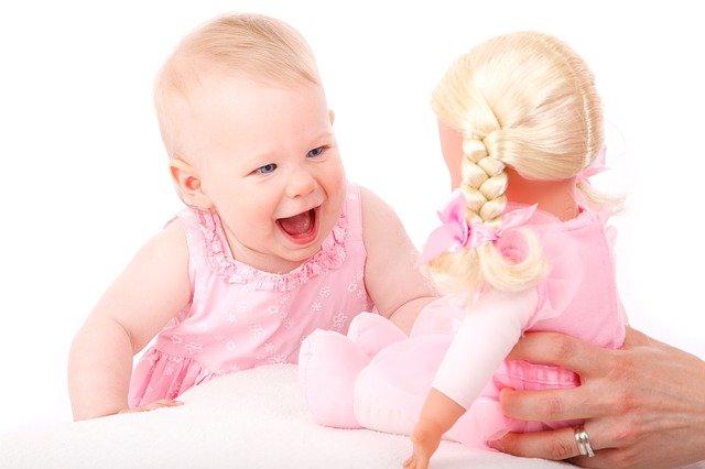 bébé qui joue avec une poupée